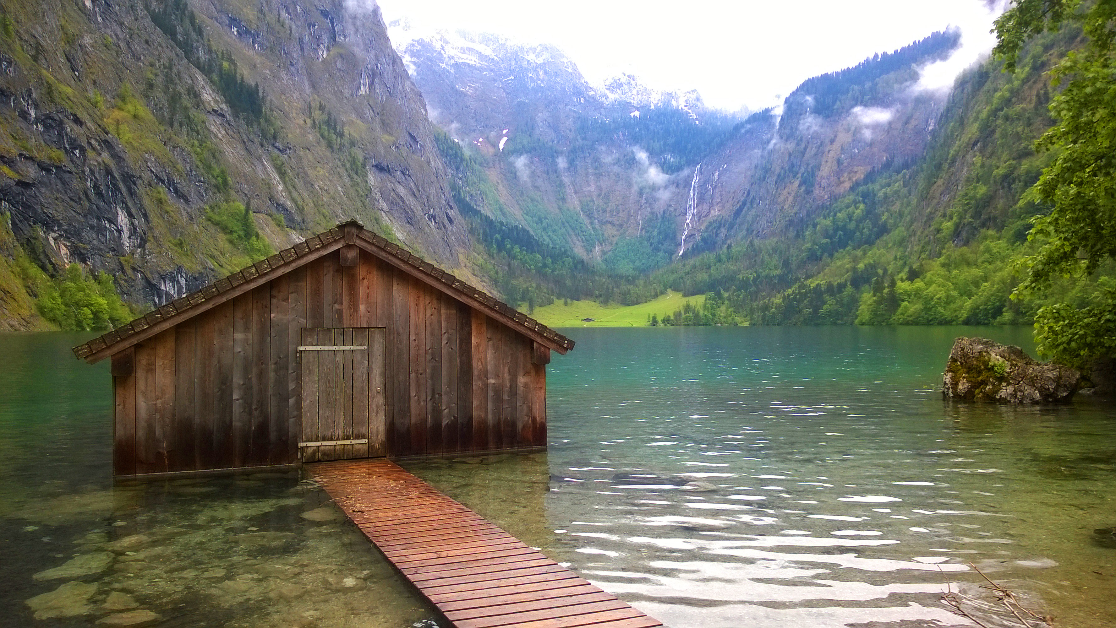 A mountain lake with a boathouse set a few metres into the water.